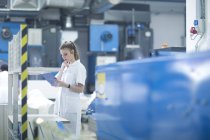 Woman working at machinery in laundry — Stock Photo
