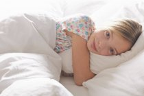 Portrait of blond haired girl hugging pillow in bed — Stock Photo