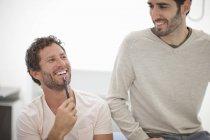 Dos colegas masculinos riendo en la oficina - foto de stock