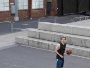 Jeune homme jouant au basketball dans la cour extérieure — Photo de stock