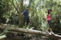 Jeunes joggeurs sur le tronc d'arbre d'équilibrage — Photo de stock