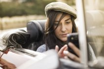 Young woman wearing flat cap in convertible using smartphone — Stock Photo