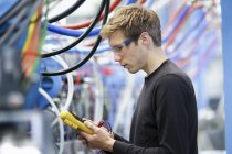 Mid adult male technician testing cables in engineering plant — Stock Photo