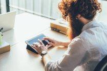 Молодые мужчины битник с красные волосы и борода, используя сенсорный экран цифровой планшет на стол — стоковое фото