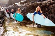 Quatre personnes transportant des planches de surf — Photo de stock