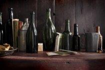 Close-up tiro de pilha de garrafas de vinho de emty na mesa de madeira — Fotografia de Stock