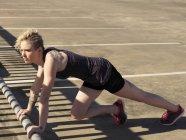 Junge Frau tut Push-up-Training in städtischen Parkplatz — Stockfoto
