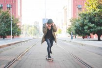 Young male skateboarder adjusting earphones whilst skateboarding on tramway — Stock Photo