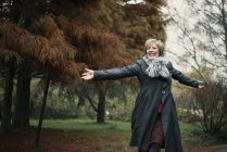 Portrait of mature woman, arms outstretched outdoors — стоковое фото