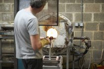 Male caucasian Glassblower in workshop using furnace — Stock Photo