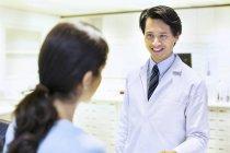 Мужчина-фармацевт выписывает рецепт клиенту — стоковое фото