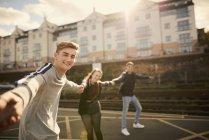Three friends fooling around outdoors, holding hands, Bristol, UK — Stock Photo