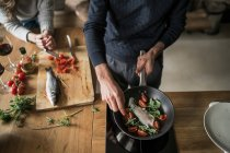 Cropped image of couple preparing fish at kitchen counter — Stock Photo