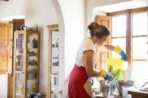 Молодая женщина наливает жидкое лавандовое мыло в миску в мыльной мастерской ручной работы — стоковое фото