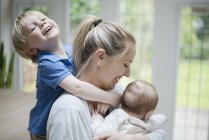 Мальчик, руки на шее матери, мать обнимает малыша. — стоковое фото