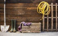 Rangée de bêche, bottes en caoutchouc et tuyau d'arrosage par hangar — Photo de stock