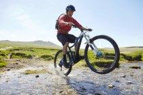 Radfahrer machen Wheelie durchs Wasser — Stockfoto