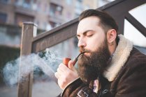 Joven barbudo pipa hombre en pasos - foto de stock