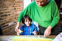 Madre ayudando a su hijo a difundir pegamento en papel crepé para hacer piñata - foto de stock