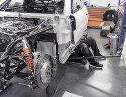 Engenheiro trabalhando debaixo do carro na fábrica de automóveis de corrida — Fotografia de Stock