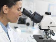 Scientifique regardant la diapositive d'échantillon pour l'essai clinique en laboratoire — Photo de stock