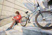 Человек сидит на шаги с Bmx с помощью смартфона — стоковое фото