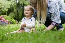 Mother with baby girl sitting on grass — Stock Photo