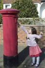 Young girl at post box, reaching up to post letter — Stock Photo