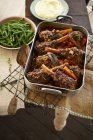 Top view of lamb shank stew in roasting tin with green beans and mashed potatoes — Stock Photo