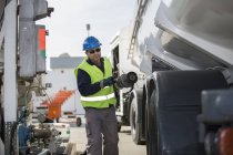 Male worker pumping fuel at fuel depot — Stock Photo