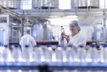 Trabajadora inspeccionando botella de agua en línea de producción en fábrica de agua de manantial - foto de stock