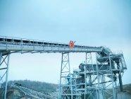 Vue à faible angle des ouvriers sur des étapes du convoyeur de criblage à la carrière — Photo de stock