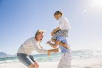 Великий брат по пляжу, несучи брат на плечі, батько лоскоту — стокове фото
