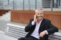 Mature man making cellphone call on bench — Stock Photo