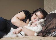 Portrait of Ragdoll cat with owner, relaxing on bed — Stock Photo