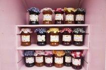 Frascos de compotas caseiras e marmelada na prateleira — Fotografia de Stock