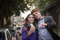Coppia che cammina lungo la strada, si abbracciano, sorridono — Foto stock