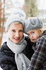 Mother carrying daughter in snow — Stock Photo