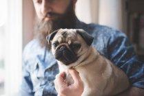 Молодой бородатый мужчина с собакой на руках — стоковое фото