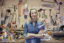 Женщина в мастерской, скрещенные руки, держащие защитные перчатки, смотрящие на улыбающуюся камеру — стоковое фото