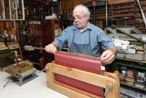 Homem sênior espinha do livro na oficina de encadernação tradicional de medição — Fotografia de Stock