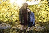 Mère et fille souriant dans zone boisée — Photo de stock