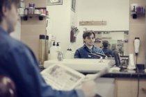 Kunde im Friseurladen Lesezeitung, Spiegelreflexion — Stockfoto