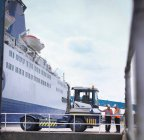 Port workers with shipping container truck and ship in port — Stock Photo