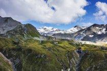 Colinas verdes e montanhas rochosas cobertas de neve sob céu nublado — Fotografia de Stock