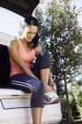 Feminino corredor amarrando cadarço na parte de trás do carro — Fotografia de Stock