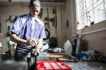 Giovane che lavora al vice in officina di riparazione — Foto stock