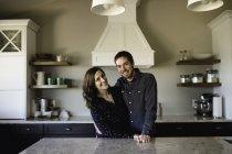 Retrato de pareja adulta en el mostrador de la cocina - foto de stock