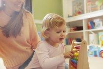 Filha adulta meados de da mulher e da criança que conta no ábaco no sala jogos — Fotografia de Stock