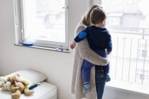 Rear view of mid adult woman and baby son looking through window — Stock Photo